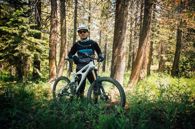 Man in forest with mountain bike, looking at camera, Mammoth Lake, California, USA, North America