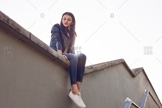 Young woman sitting on roof, low angle view