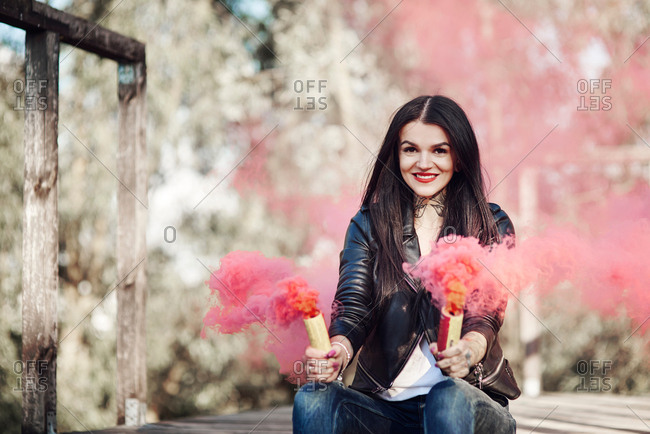 Young woman sitting on decking, holding smoke flares, smoke pouring from flares