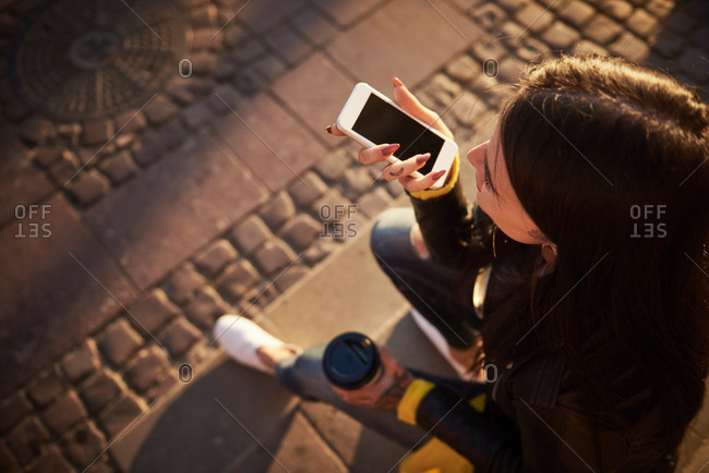 Young woman sitting outdoors, holding coffee cup, using smartphone, tattoos on hands, elevated view