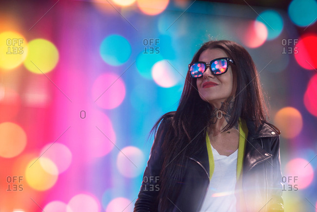 Portrait of young woman, outdoors at night, lights reflected in glasses