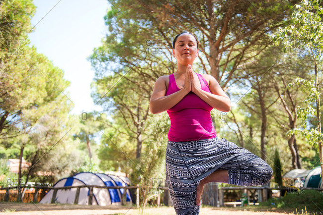 Mature woman practicing yoga tree pose on camping site