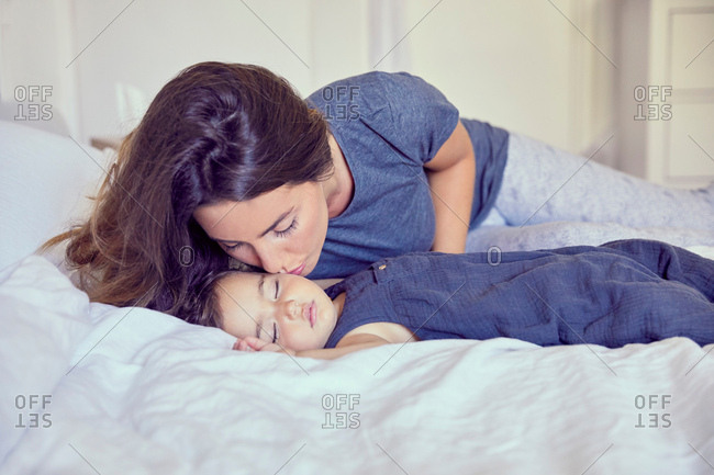Mother kidding sleeping toddler on cheek