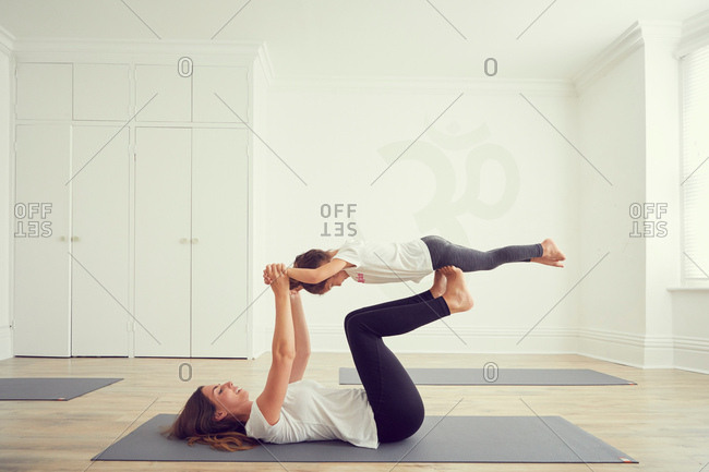 Mother and daughter in yoga studio, daughter balancing on mothers legs