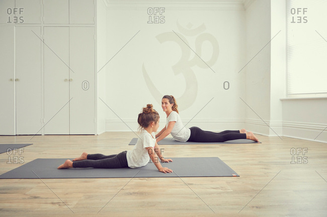 Mother and daughter in yoga studio, in yoga positions