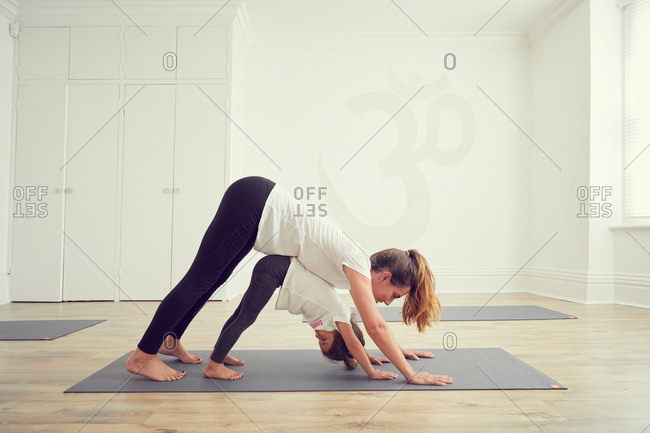 Mother and daughter in yoga studio, standing together in yoga position