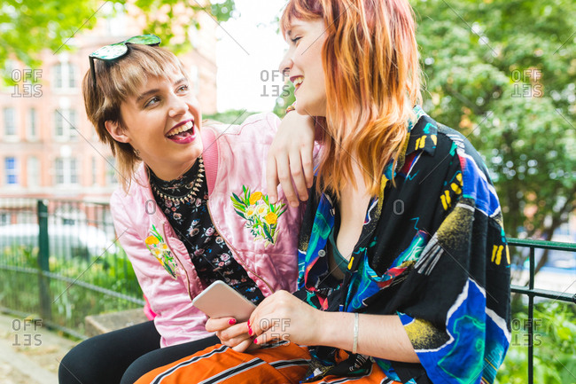 Two retro styled young women laughing in park