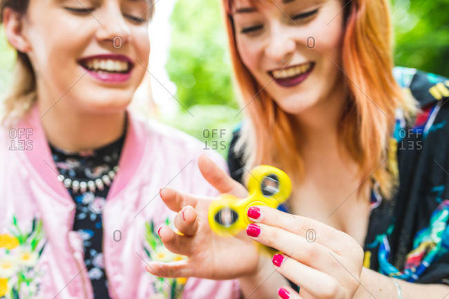 Two retro styled young women playing with fidget spinner in park