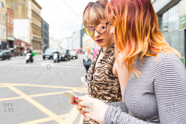 Two retro styled young women strolling along city street looking at smartphone
