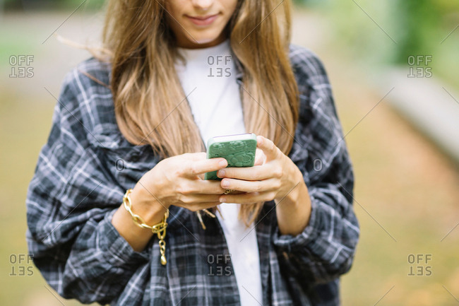 Cropped shot of young woman using smartphone touchscreen in park