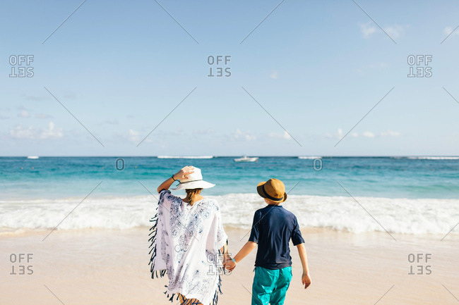 Mother and son, holding hands,standing on beach, looking at view, rear view