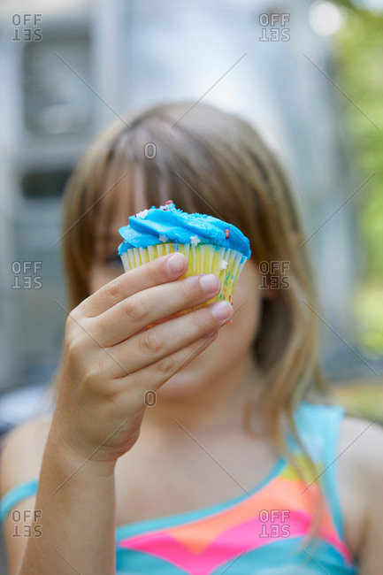 Young girl holding cupcake