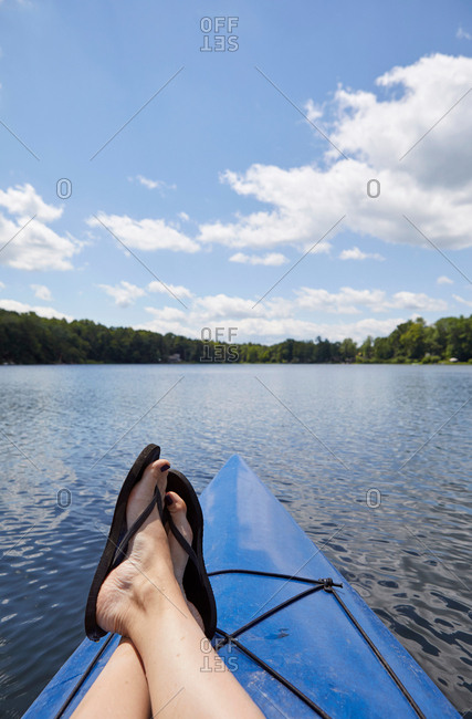 Woman relaxing on canoe, on lake, low section