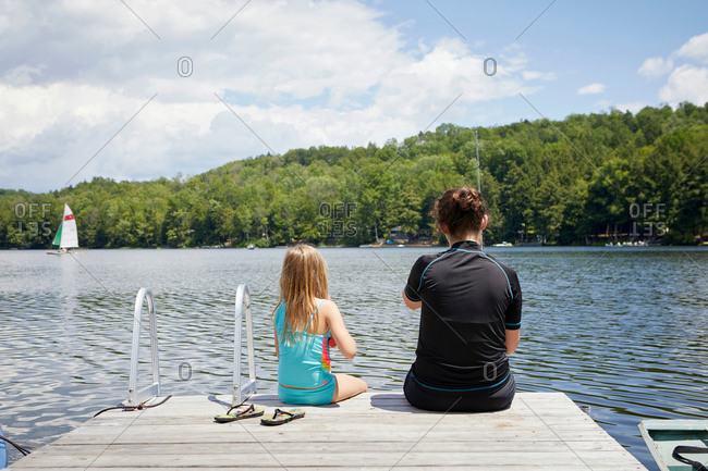 Two young girls sitting on jetty, rear view
