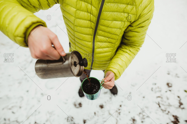 High angle neck down view of male hiker pouring coffee from flask in snow