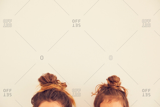Portrait of mother and daughter, hair in bun, top section