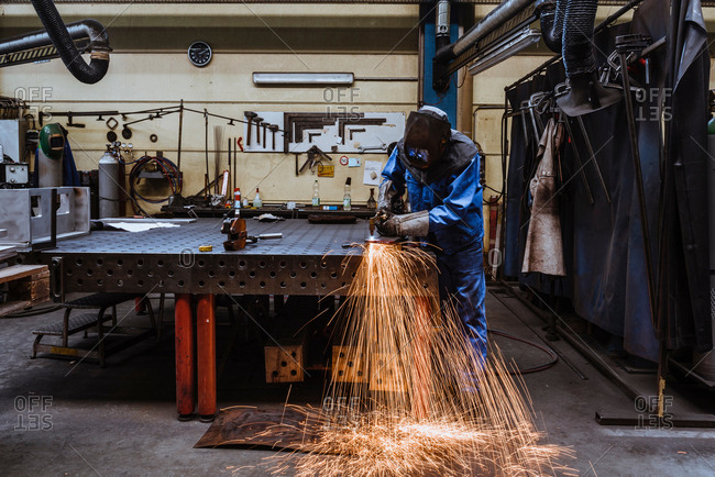Man in welding mask cutting steel in factory