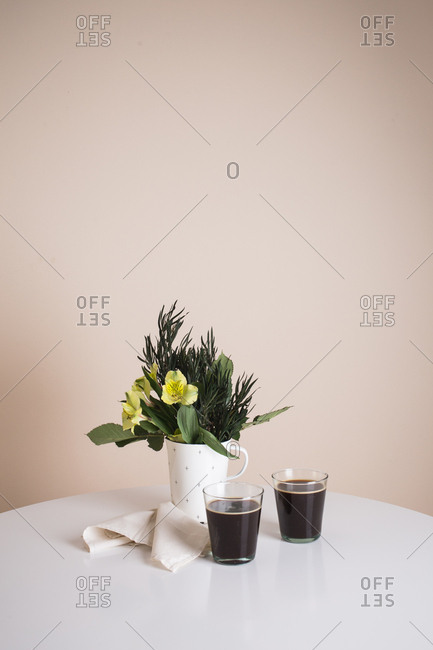 Glasses filled with coffee on table with floral arrangement in cup