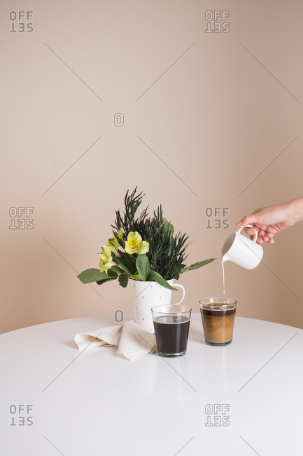 Person adding cream to a cup of coffee