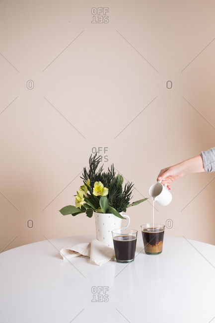 Person pouring cream into a cup of coffee