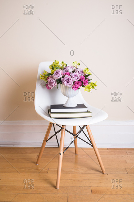 Floral arrangement and books on chair