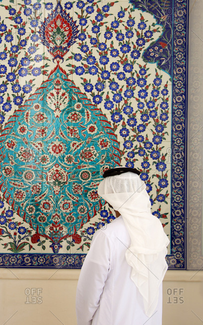 Abu Dhabi, United Arab Emirates - September 14, 2012: Person looking at decorative tiled wall at Sheikh Zayed mosque