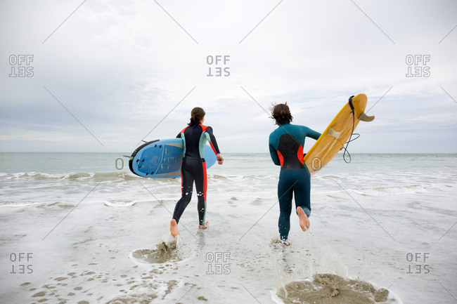Two girls carrying surfboards running into surf