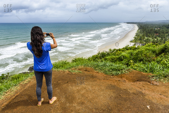 Rear view shot of woman taking picture of beach with smartphone, Itacare, South Bahia, Brazil