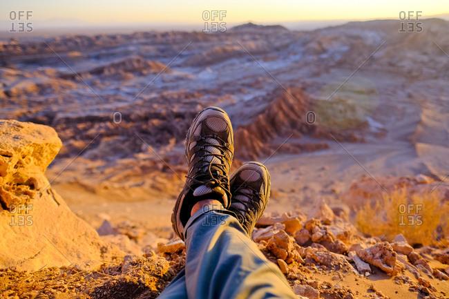 Hiker resting during sunset over Valle de La Luna in Atacama Desert outside of San Pedro de Atacama, Chile