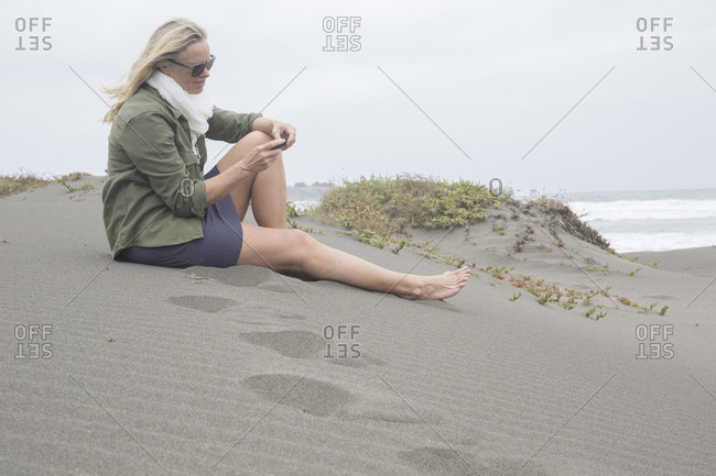 Woman sends text from coastal dune, foggy day