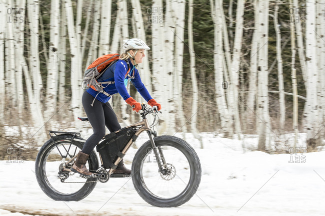 A woman riding a fat tire bike in front of aspen trees in La Plata Canyon, Mayday, Colorado.