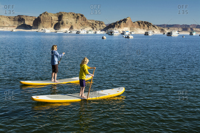 A mother and daughter paddleboarding on Lake Powell, Wahweap Marina, Glen Caynon National Recreation Area, Page,  Arizona.