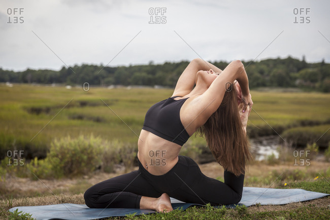 Beautiful Young Woman In King Pigeon Yoga Pose On A Yoga Mat At Sunset