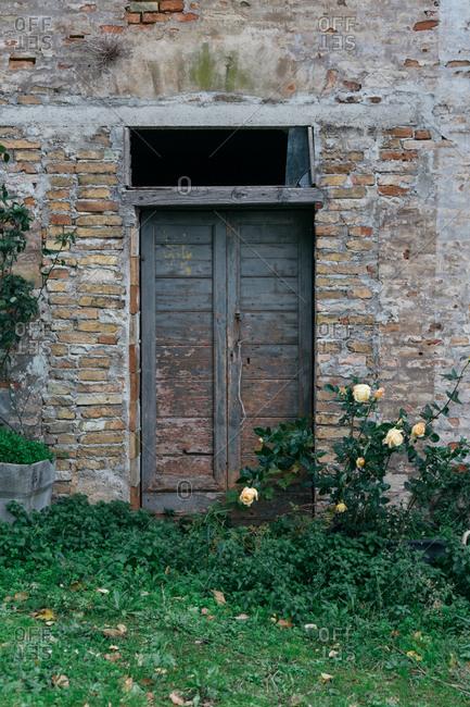 Old wooden door on brick building, Senigallia, Marche, Italy
