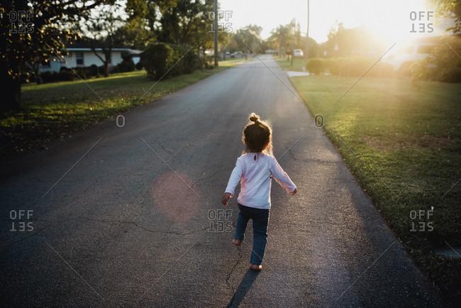 Toddler running down road barefoot