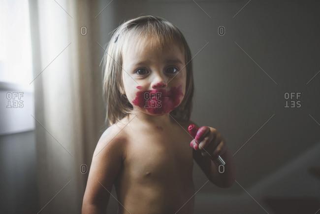 Toddler putting on lipstick
