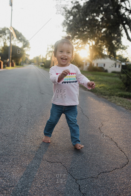 Toddler in road smiling big