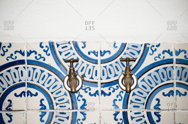 Two faucets on blue and white pattern tiled wall