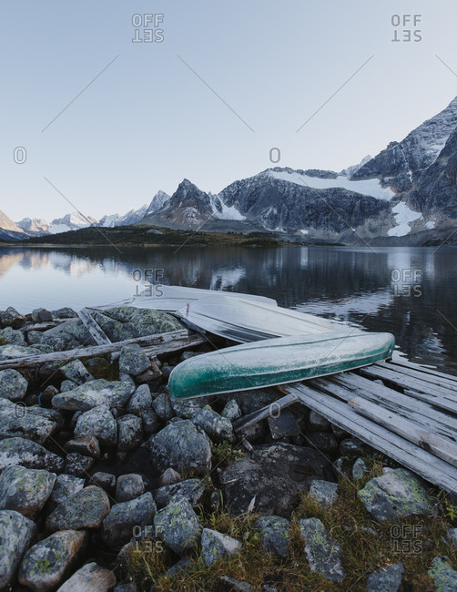 Canoes flipped over at a mountainside lake
