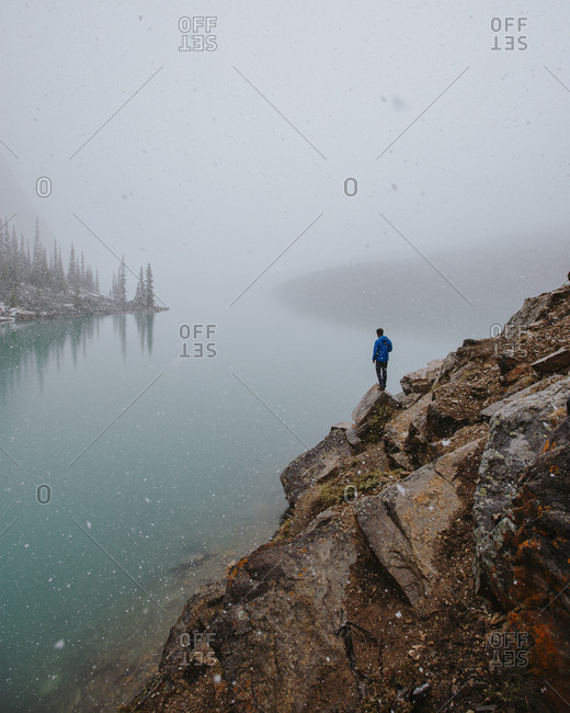 Man overlooking lake during snow from a rocky mountainside