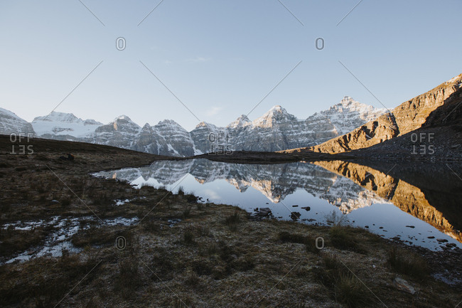 Snowy mountain reflecting in a lake at sunrise
