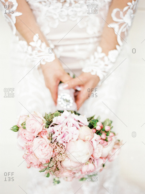 Bride holding wedding bouquet with pink roses