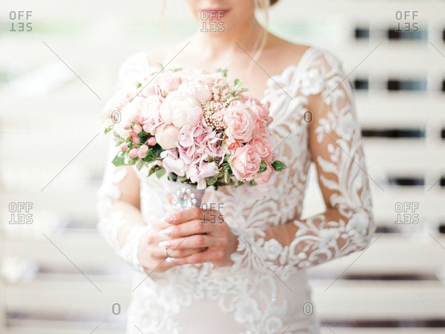 Bride holding wedding bouquet with pink flowers