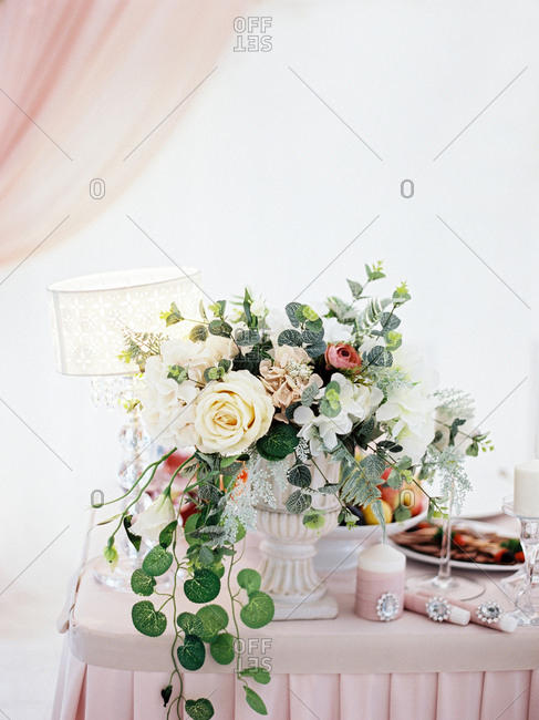 Floral arrangement with candles, lamp, and food on table at wedding