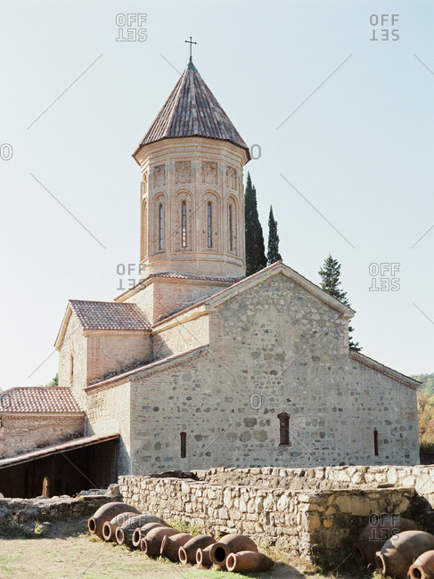 Historic stone church with stone wall and pots