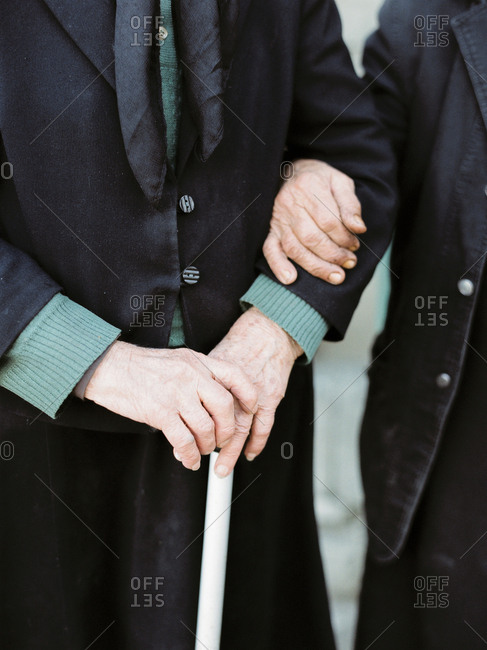 Couple standing arm in arm with cane