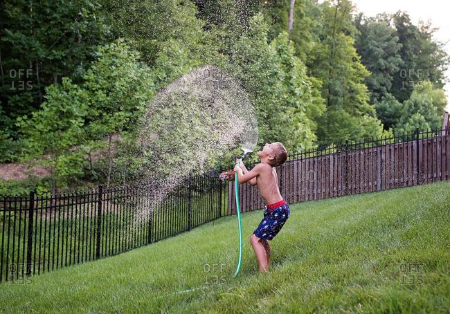 Boy holding sprinkler in the air