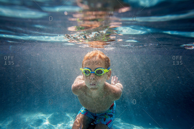 Underwater view of boy wearing goggles while swimming