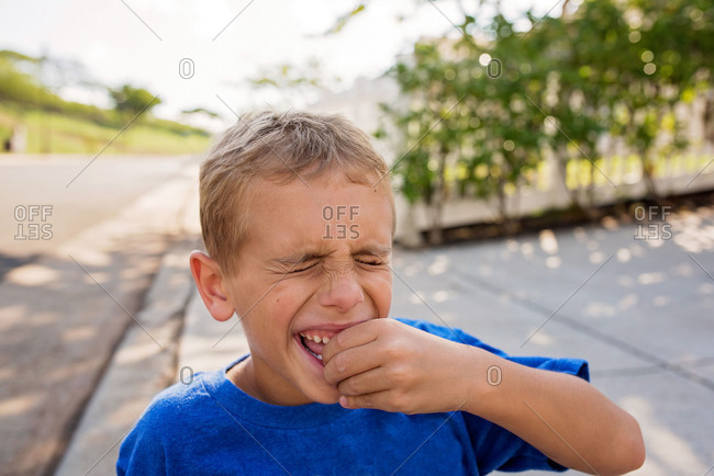 Young boy wiggling a loose tooth
