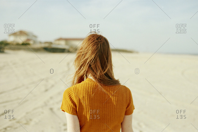 Back view of woman walking on the beach